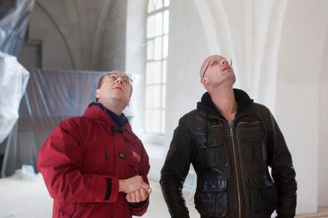 Hier ziet u twee bouwkundige staren naar een van de werkzaamheden: herstel van de schilderingen.